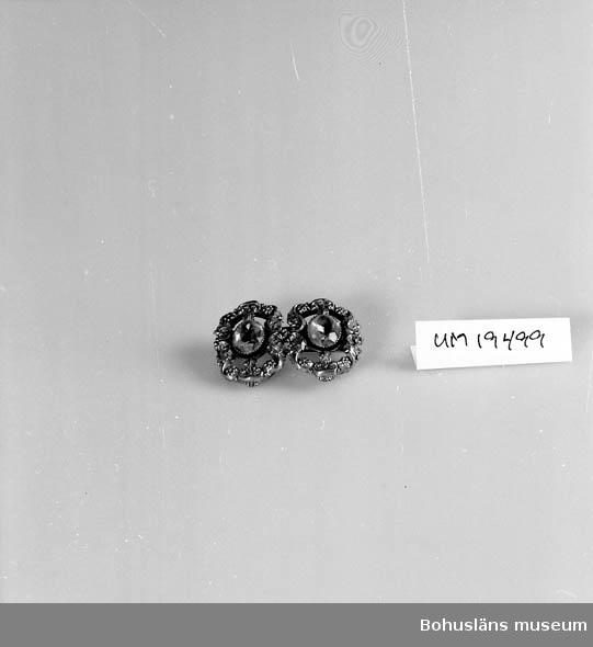 594 Landskap BOHUSLÄN 503 Kön KVINNA  Brosch tillverkad av två skospännen. Gulmetall med två ljusblå stenar/ glasbitar.  Kommer från Birgit Hambergs hem i Bengtsfors. Se UM019490.
