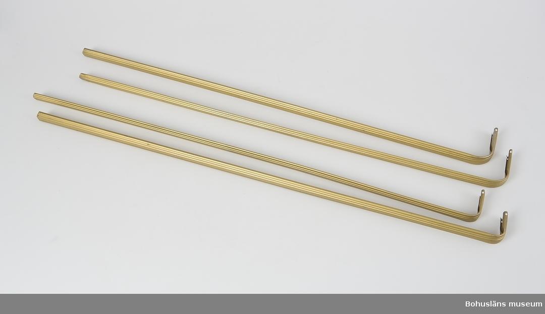 Gardinstång (yttre) med fästen 2 st samt 4 skruvar hör ihop med innerstång UM019807:2. Tillverkad av pressad järnplåt och målade med gulgrön metallglänsande färg.  Består av två delar, där den ena skjuts in i den andra. Passar till gardiner liknande UM018042 - UM018044.