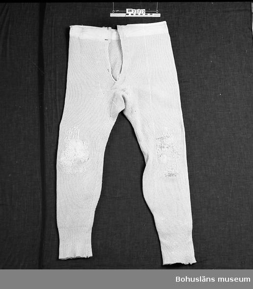 Värmande underplagg för man. Stickade, i linningen kant av naturfärgat bomullstyg och med 1 knapp. I gylfen en tygklädd metallknapp. Stopp av ulltråd på knäna och baktill på baken, samt förstärkningar i grenen. Resårstickning längre ner på benen.