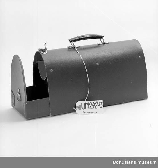 """410 Mått/Vikt !L: 34,5 B: 15 H: 18 CM 601 Röd/brun målad. Form: från sidan ser den ut som en halv oval. Väskan 602 öppnas från sidan genom att en låda dras ut. Lådan stängs med ett 603 spänne. Inne i lådan är det två """"våningar"""". Handtag på ovansidan 604 gjord av metall. 605 Väskan är gjord av papp. Lådan som dras ut är förstärkt med trä. 606 På träförstärkningen står det tryckt: """"Patents. nr 2107/45."""