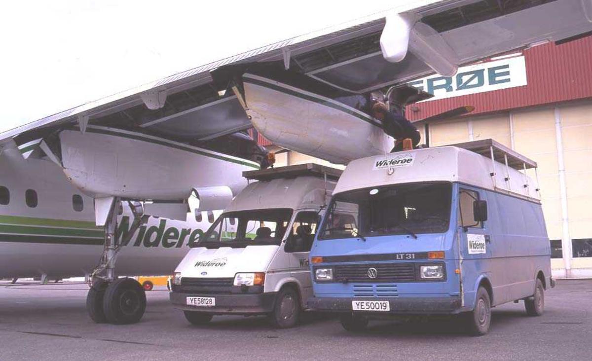 Lufthavn/flyplass. Bodø. Widerøes hangar. Ett fly, LN-WFE, DHC-7-102/ Dash7 fra Widerøe parkert. Flyteknikere inspiserer og tar vedlikehold.