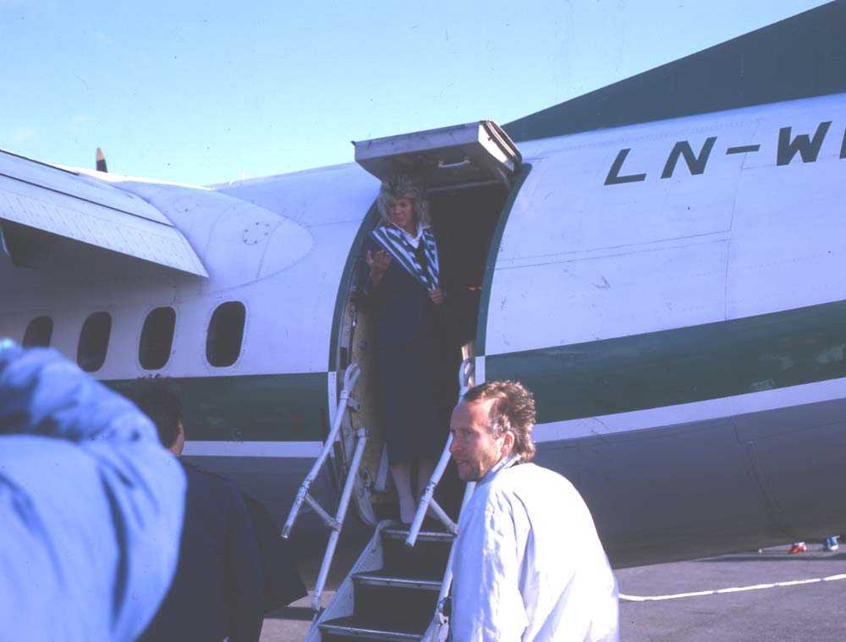 Lufthavn/flyplass. Stokmarknes/Skagen. En kabinpersonale og flere passasjerer foretar ombordstigning. Ett fly, LN-WFE, DHC-7-102/ Dash7, fra Widerøe.