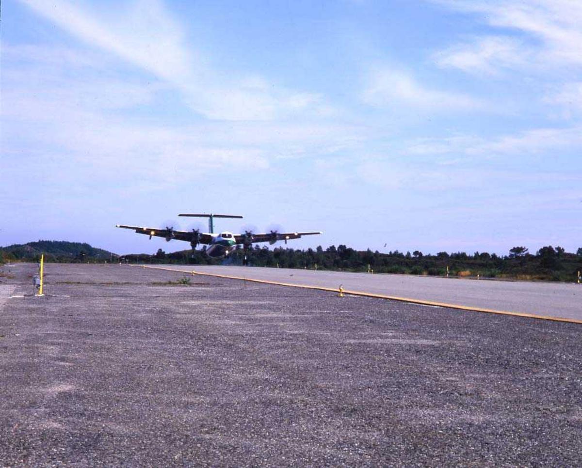 Lufthavn/flyplass. Florø. Ett fly, DHC-7-102/ Dash 7 fra Widerøe, lander runway 25.
