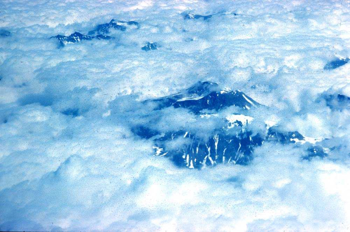 Luftfoto. Deler av Sunnmørsalpene vises mellom skyene.