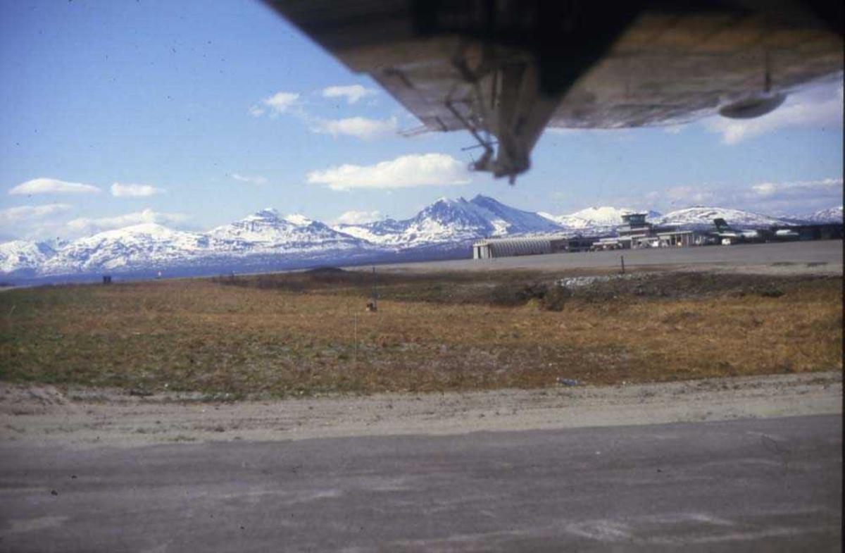 Lufthavn/flyplass. Et sted i nord. Et fly,  DHC-7-102 Dash7 fra Widerøe parkert. En underside av vingen med vinterkledde fjell i bakgrunnen.