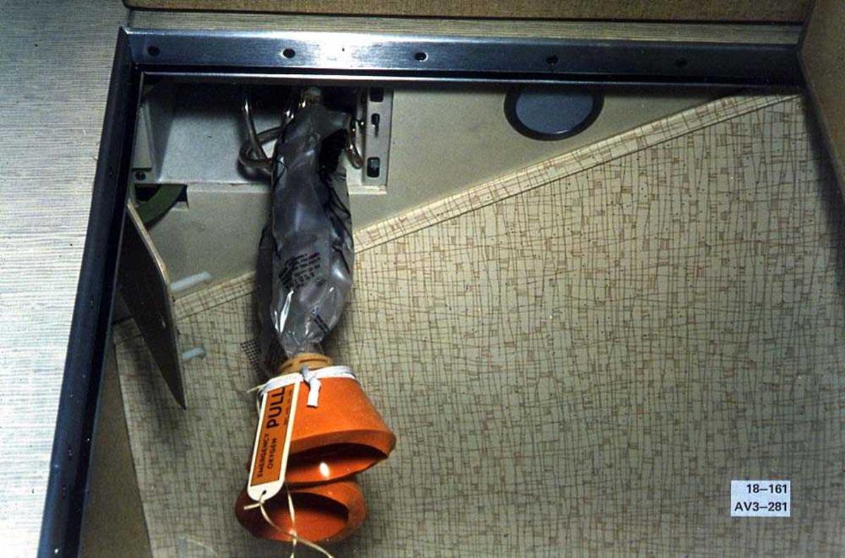 To oksygenmasker som henger ned fra en luke, i en Boeing 737-200.