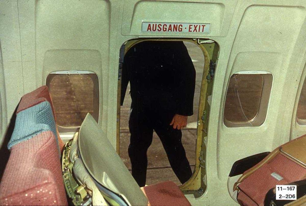 En åpen nødutgang på ett fly, Boeing 737-200. En person på utsiden av nødutgangen.
