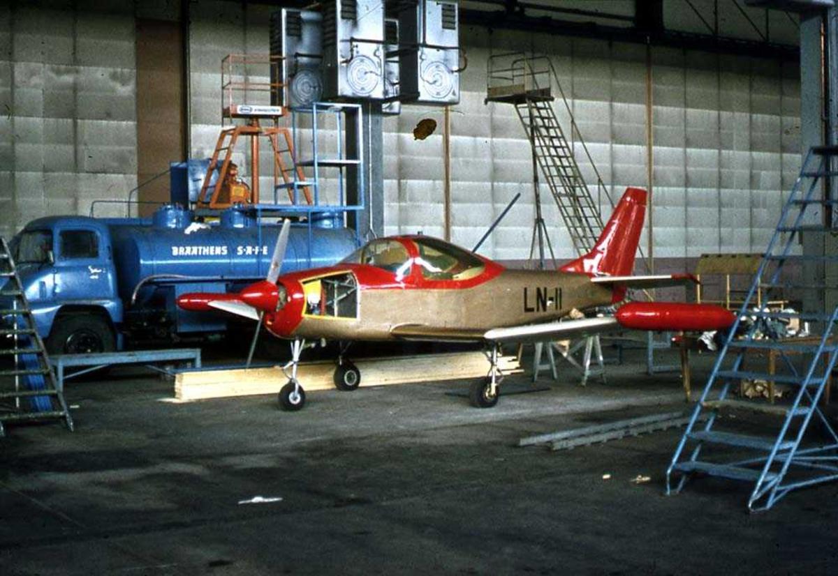 Ett fly inne i en hangar, C. L. Larsen Spesial I/II LN-11 / LN-LMI. Ett kjøretøy bak flyet.