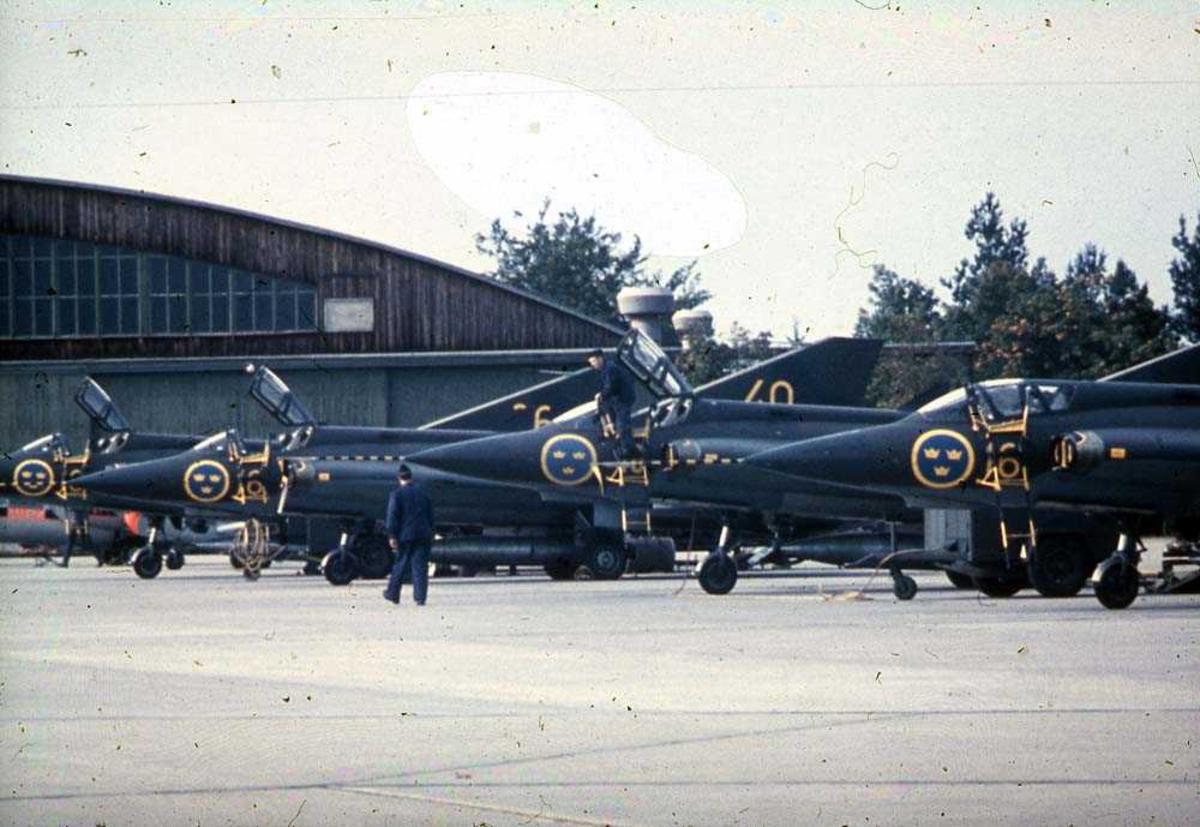 Lufthavn. Fire fly på bakken, Saab J35 Draken. Bygning i bakgrunnen.