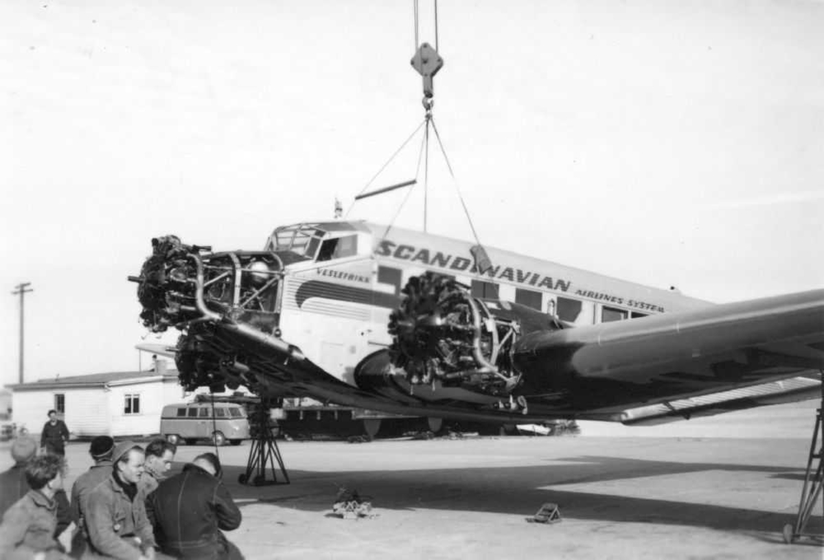 Lufthavn (flyplass) Ett fly henger i heisekran, SAS Ju-52 fra SAS. Understellet og motorbeslag er fjernet (ettersyn).