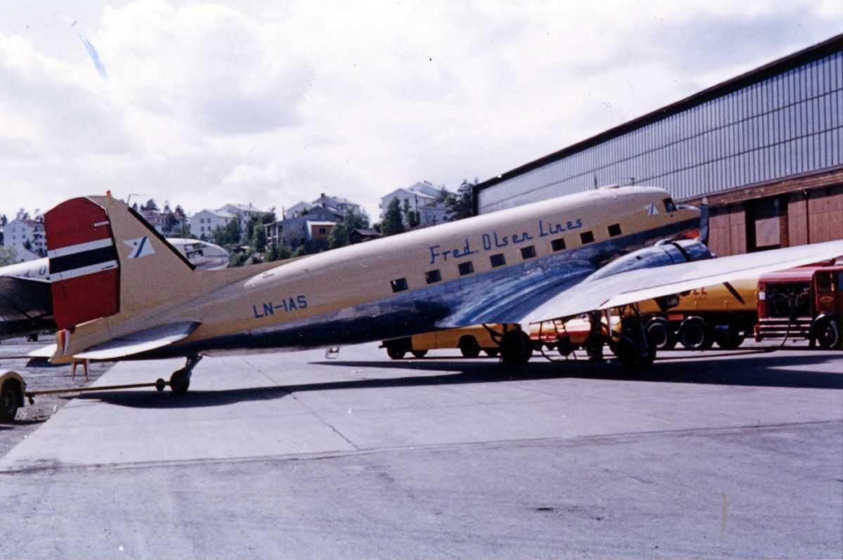 Lufthavn. Ett fly på bakken, DC-3 Dakota LN-IAS fra Fred Olsen. Bygninger i bakgrunnen.