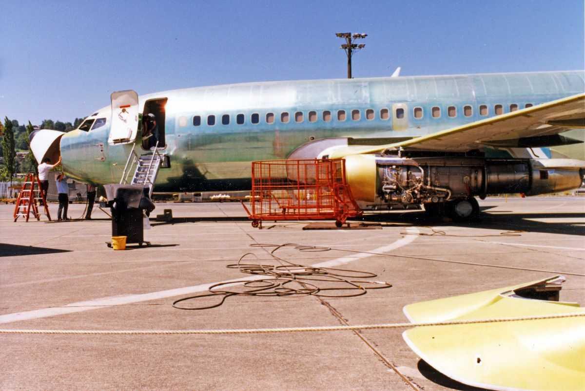 Lufthavn. Ett fly på bakken, Boeing 737-200, som blir klargjort for levering til Braathens SAFE.