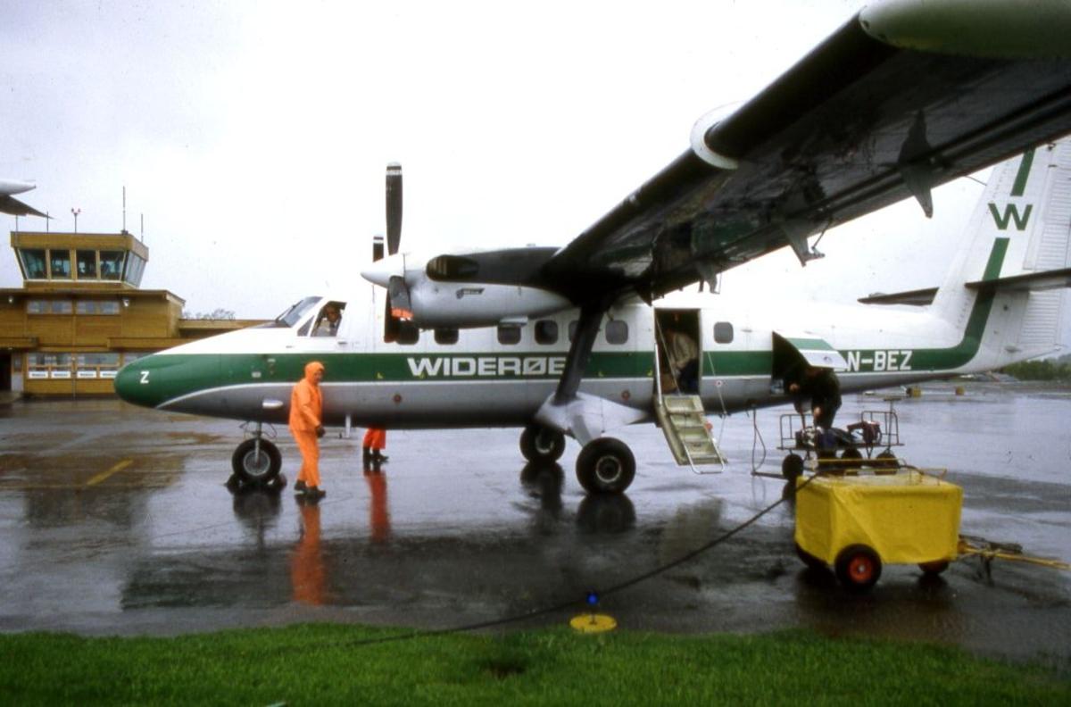 Lufthavn (flyplass). Et fly, LN-BEZ, DHC-6-300 Twin Otter fra Widerøe To personer arbeider på oppstillingsplassen (tarmac).