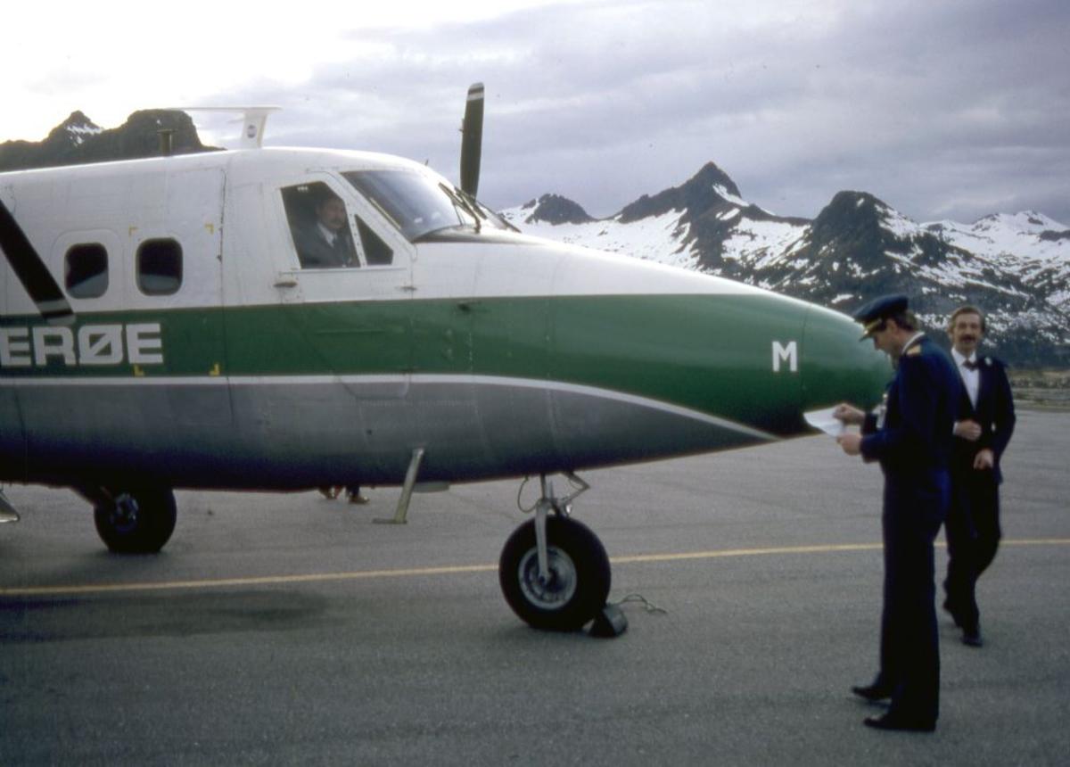 Lufthavn (flyplass). Et fly, LN-BNM, DHC-6-300 Twin Otter fra Widerøe. To personer utenfor flyet, flyger (pilot) og passasjer. I cockpit skimtes en person (pilot).