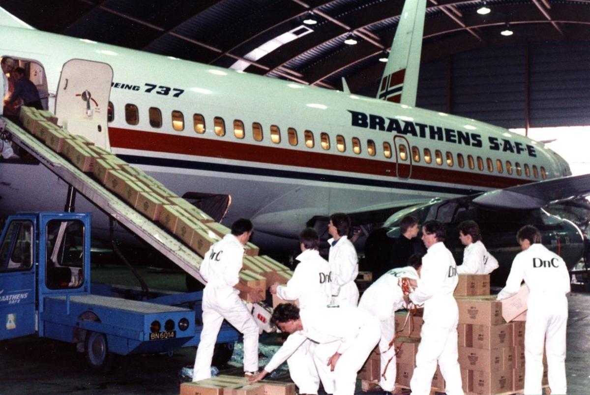 Flyplass/Lufthavn. Flere personer fra Braathens SAFE, laster en Boeing 737 opp med frakt/cargo på et transportbånd.