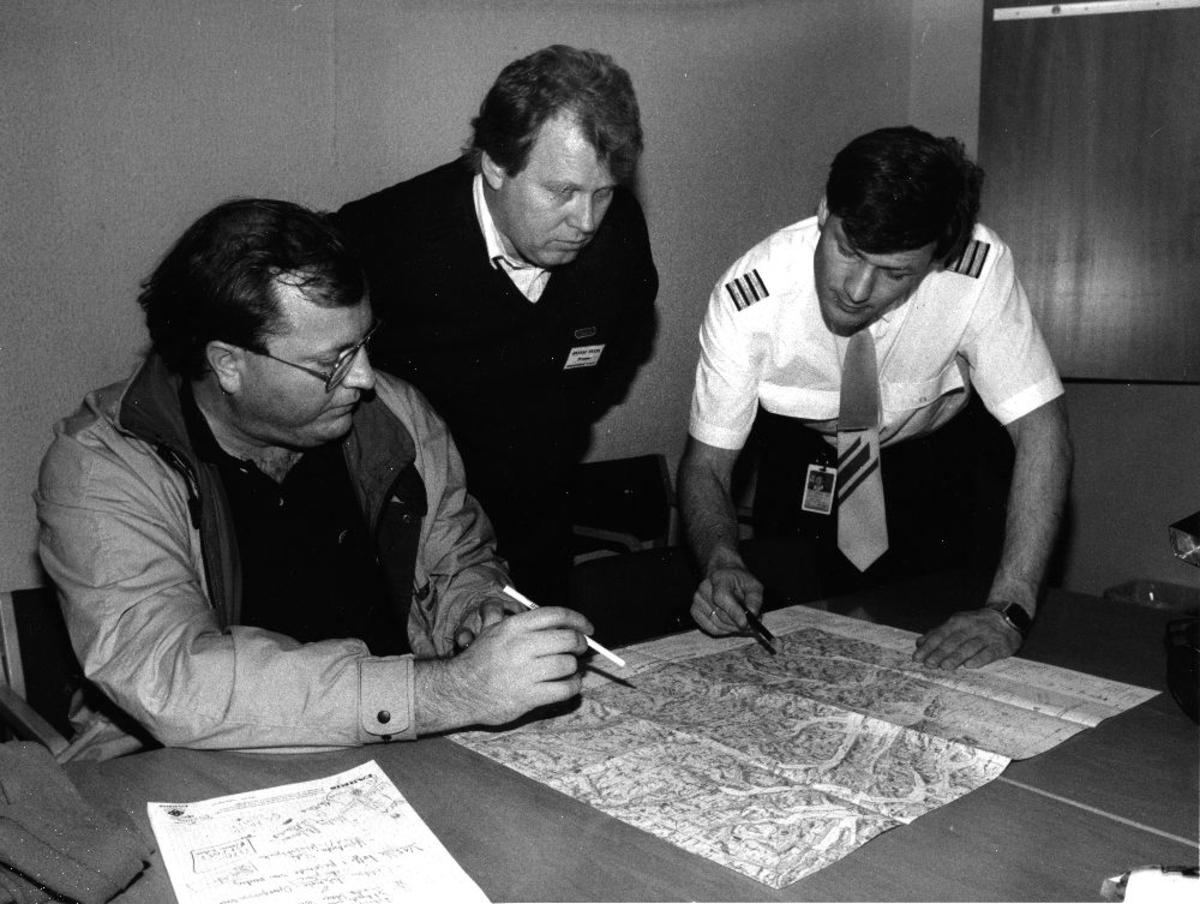 """Landskap. Tre personer fra Braathens SAFE studerer et kart  under  """"Øvelse Delta"""""""