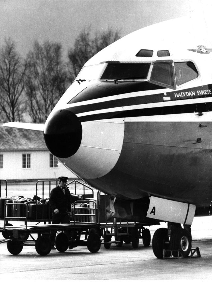 "Lufthavn/Flyplass. Et fly, Boeing 737-205, LN-SUA, ""Halvdan Svarte"", fra Braathens SAFE. En person med flere bagasje traller."