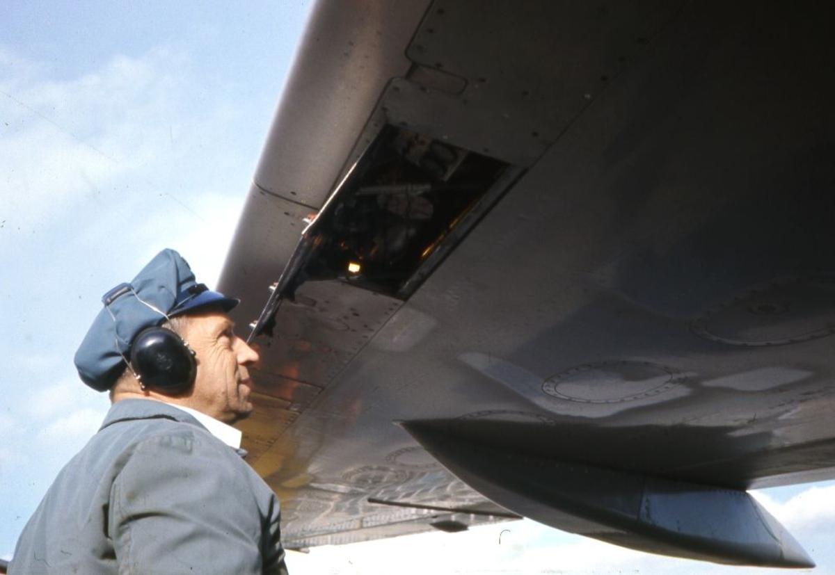 Lufthavn/Flyplass. En person har åpnet en luke og kontrollerer kontakten under vingen for brennatoffsystemet til et fly fra Braathens SAFE.