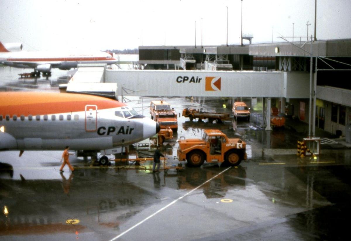 Lufthavn/Flyplass. Et fly fra CP Air nettopp tauet til dokk av en truck. Noe aktivitet rundt flyet.