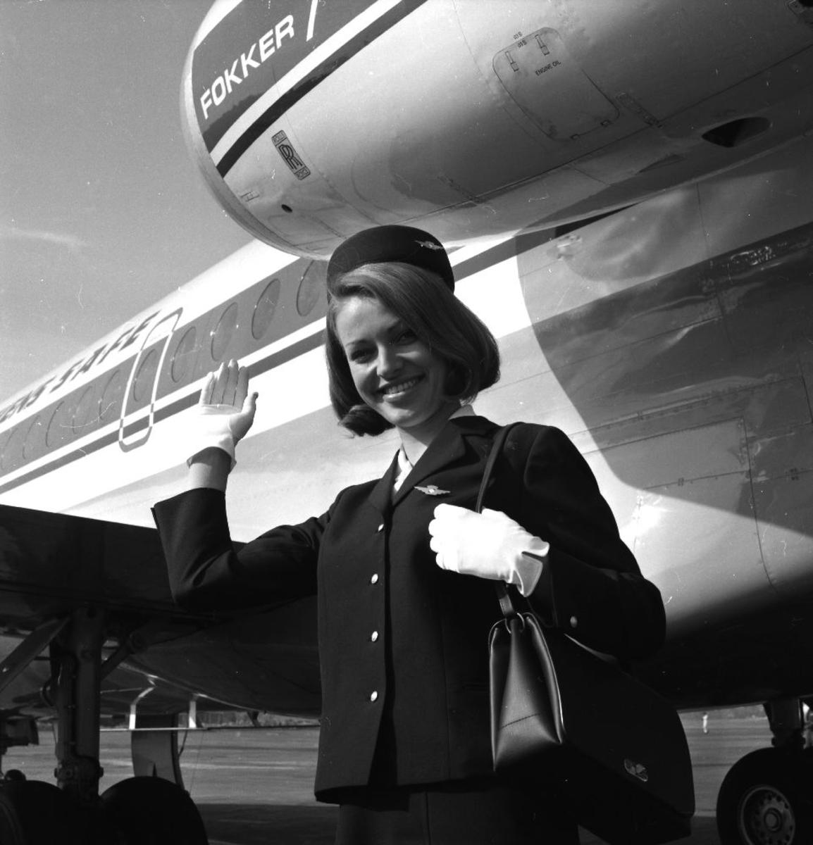 Lufthavn/Flyplass. Et fly, Fokker F-28 Fellowship og en blid kabinansatt/flyvertinne fra Braathens SAFE, ønsker velkommen ombord.