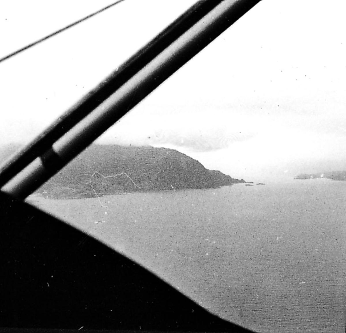 Luftfoto tatt fra fly. Land og hav under.