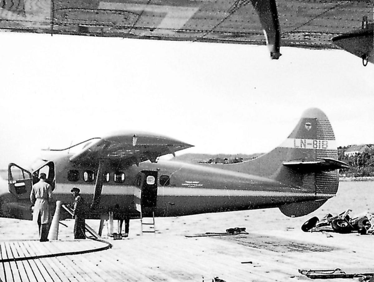 1 fly ligger ved kai og fyller drivstoff, DHC.3 Otter, LN-BIB.  2 personer ved flyet. Litt av vingen på annet fly i forgrunnen.