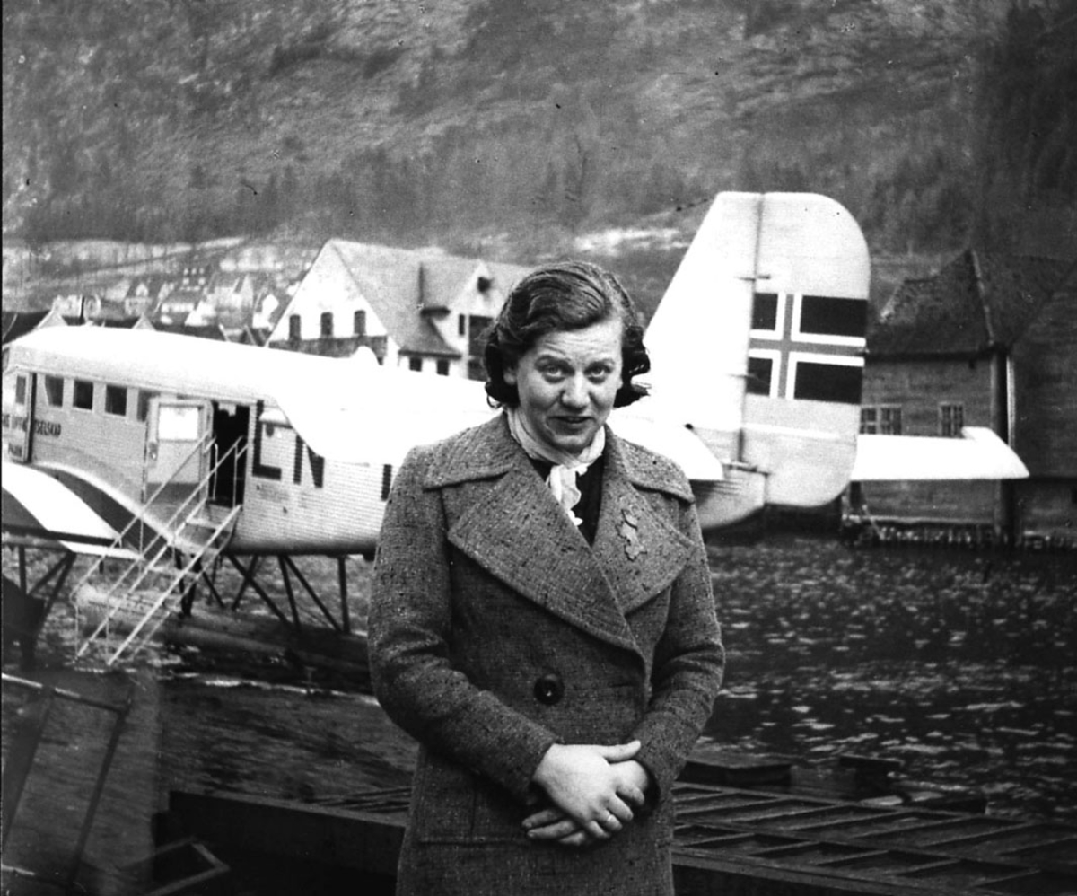 """Sjøflyhavn. Portrett, en person foran ett fly på vannet, Junkers JU-52, (LN-DAH """"Falken"""")?. Flere bygninger i bakgrunnen."""