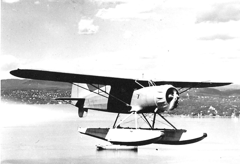 Luftfoto, ett fly, Hønningstad C5          Polar ser no 1., like over havflata. Sjøfly.   Bebyggelse bak.