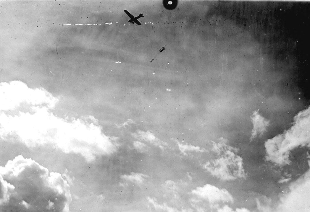 Luftfoto, ett fly i luften, fallskjermslipp fra Fokker CVE. Bildet tatt fra bakken.