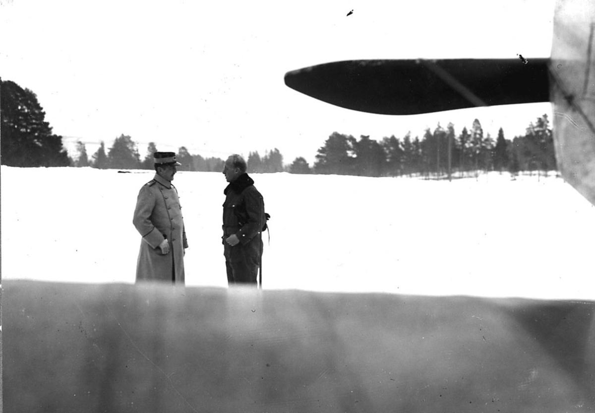To personer. Svensk flyoffiser i samtale med norsk løytnant. Snø på bakken. Litt av ett fly sees i høyre billedkant.