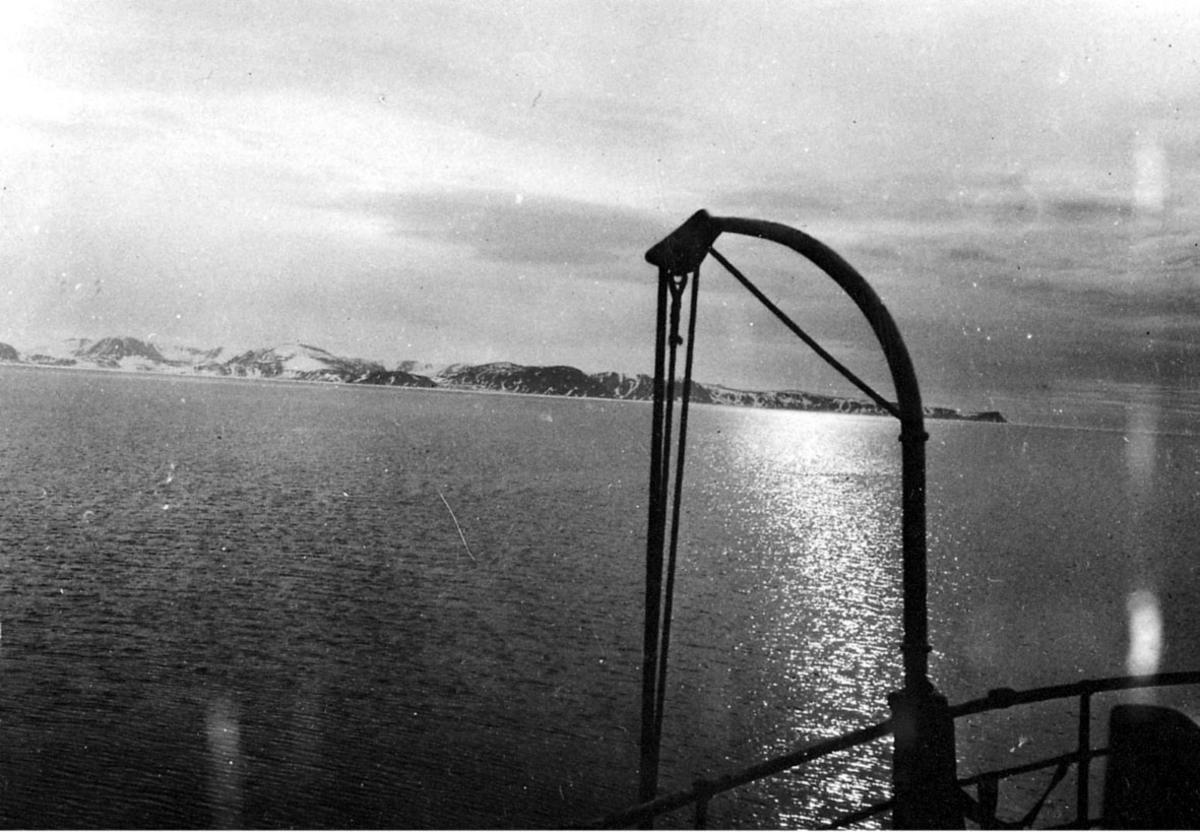 Bilde tatt fra en en båt, en av davidene i forgrunnen. Hav og fjell bak.