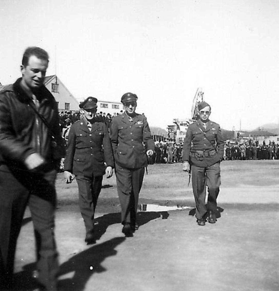 Frigjøringsdagene i Bodø etter krigen 1940 - 1945. Åpen plass, militære og sivile personer samlet. Kullkranen til Jakhelln bak.