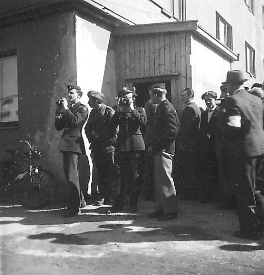 Frigjøringsdagene i Bodø etter krigen  1945. Noen militære og sivile personer foran bygning. Noen med fotoapparat.