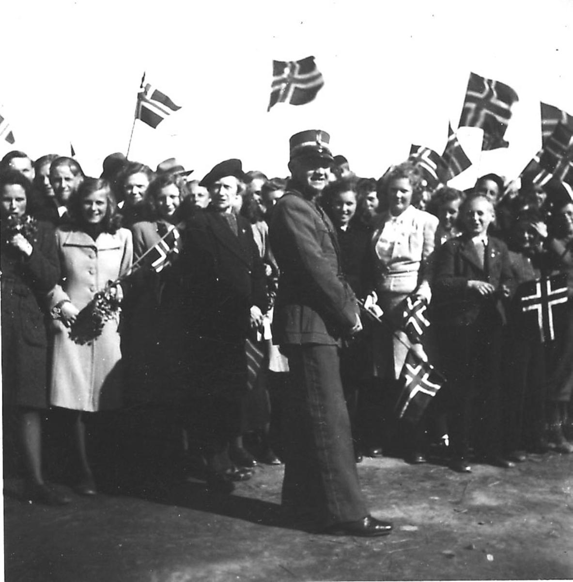 Frigjøringsdagene i Bodø etter krigen  1945. Flere personer, noen med flagg. En person i uniform foran.