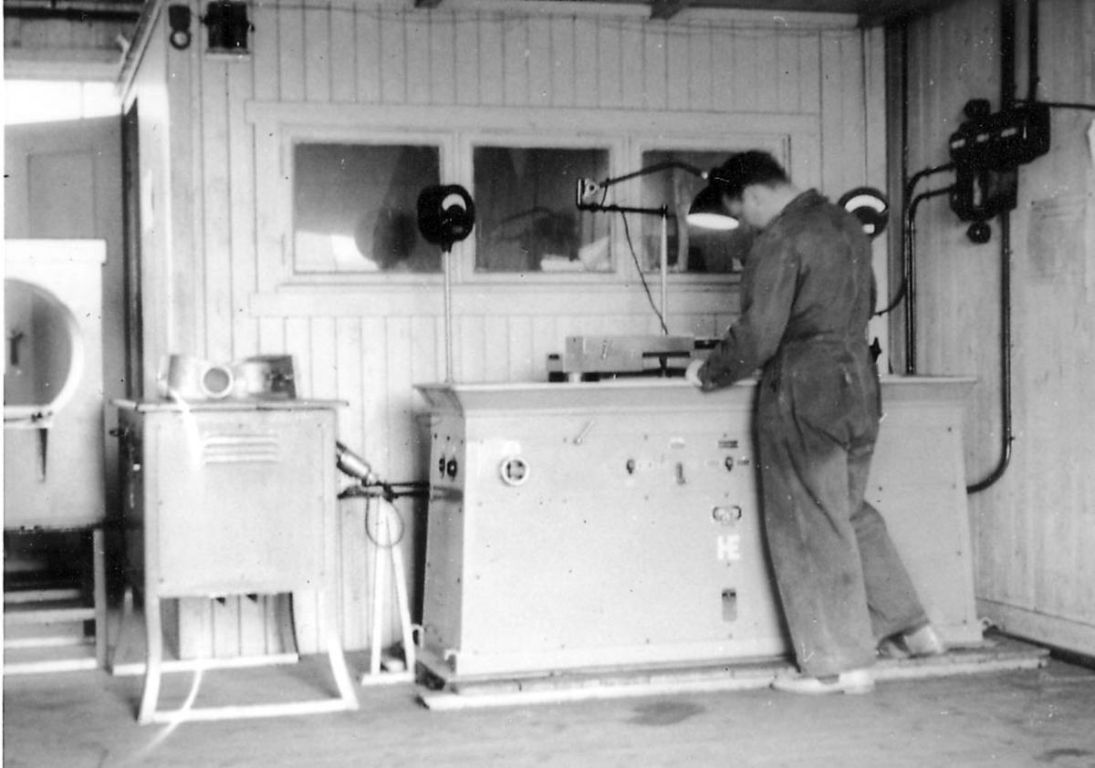 Interiør fra verksted.   En person, verkstedarbeider/mekaniker, i arbeid.