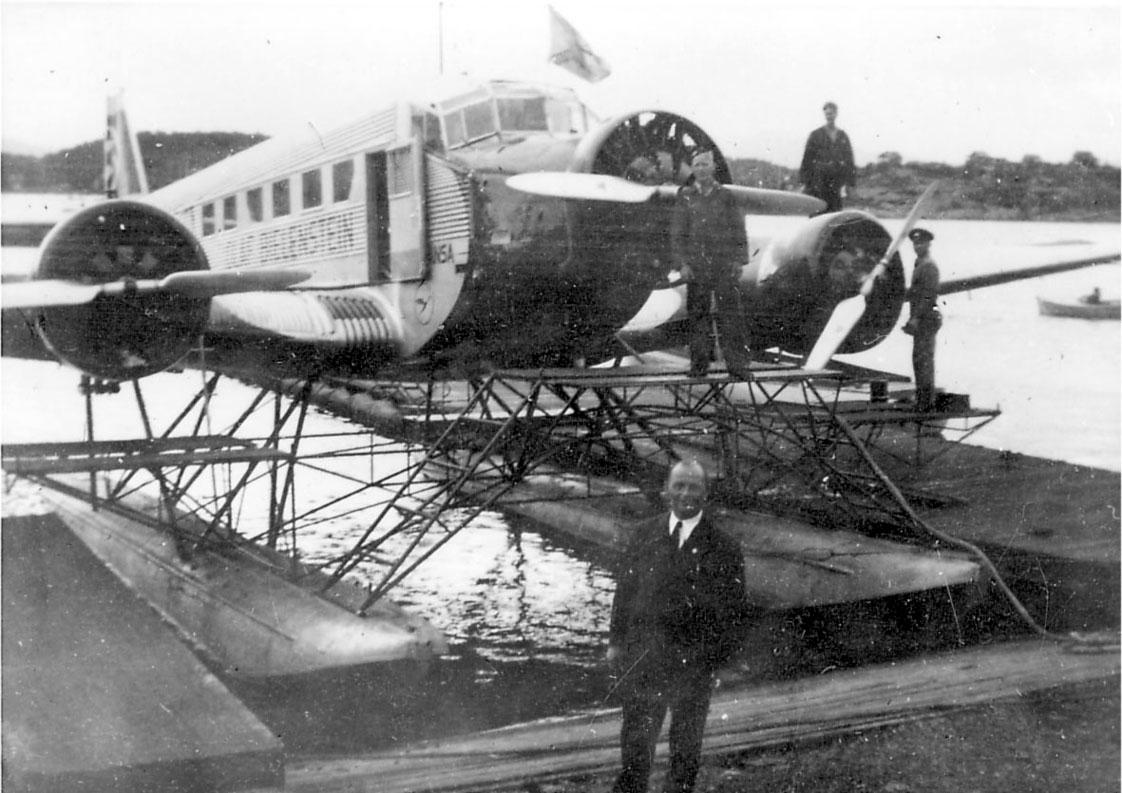 Sjøflyhavn, ett fly i vannkanten, Junkers Ju 52/3mg3e, fra lufthansa. Flere personer ved flyet. Flytebrygge/kai.