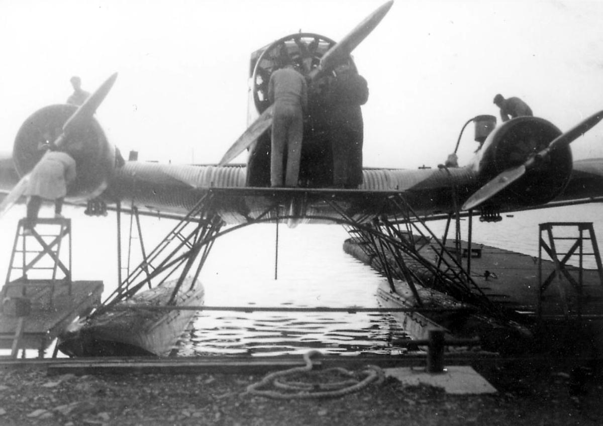 Sjøflyhavn, ett fly i vannkanten, Junkers Ju 52/3mg3e. Flere personer, ant. mekanikere, arbeider med flyet. Flytebrygge/kai.