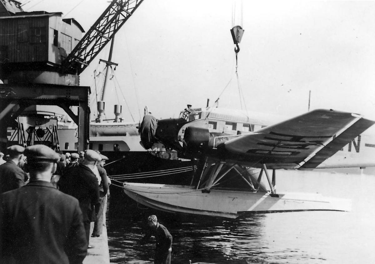 """Ett fly, Junkers Ju 52/3mg2e, LN-DAH, """"Falken"""". Henger i heisekran. Flere personer ved flyet. Litt av overbygg på en båt i bakgrunnen."""