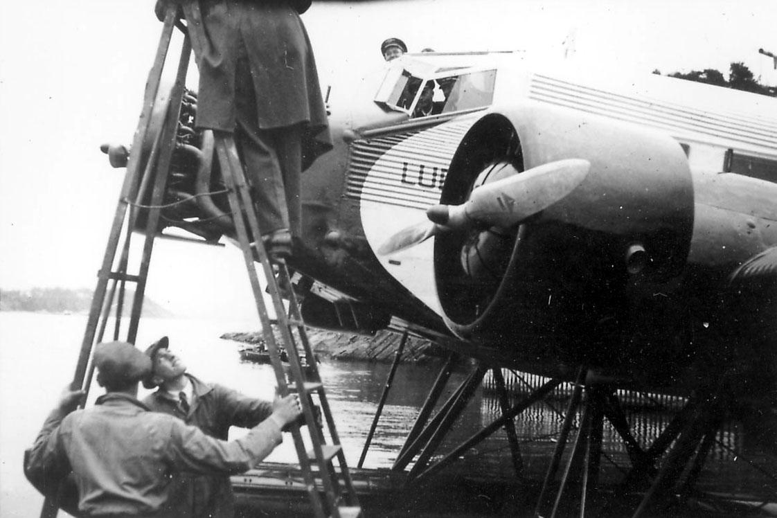 ett fly i vannkanten, Junkers Ju 52/3mg3e. Flere personer, mekanikere, en står i en stige.