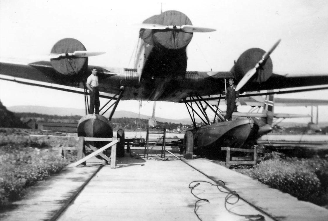 Sjøflyhavn, ett fly på bakken, Junkers Ju 52/3mg3e. Presenninger over motorene. to personer ved flyet. Litt av ett annet fly sees i bakgrunnen.