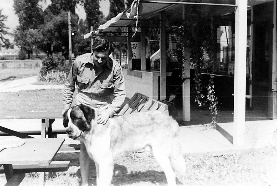 Portrett, en person, militær, i militæruniform sammen med en større hund. Bygning bak (innebygd veranda).