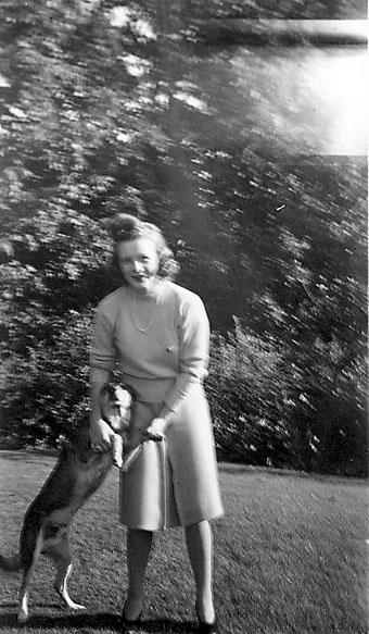 Portrett, person, ant. i en park, leker med en hund. Ung kvinne i sivile klær. Bildet har engelsk tekst på baksiden som er skrevet for hånd