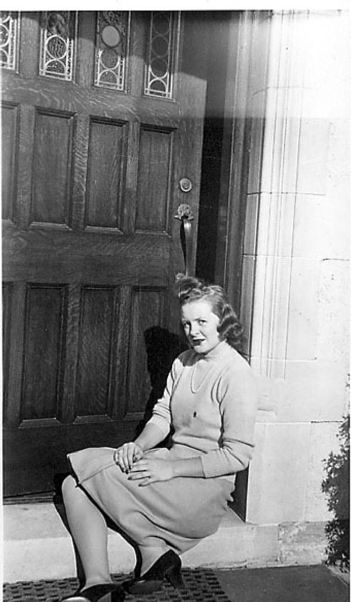 Portrett, en person sitter på trappa foran inngangen til ei bygning. Ung kvinne i sivile klær.