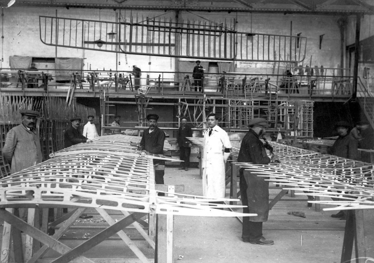 Interiør fra flyfabrikk, verksted, e.l. Flere personer i arbeid med bygging, reparasjoner, på bl.a. flyvinger