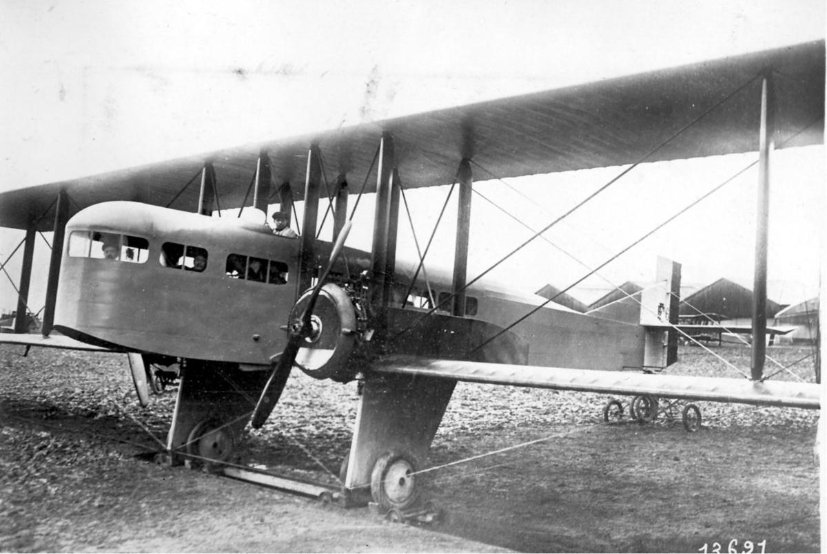 Fly, Maurice Farman F60. Skrått forfra. Står på bakken. Bygninger - hangarer bak.