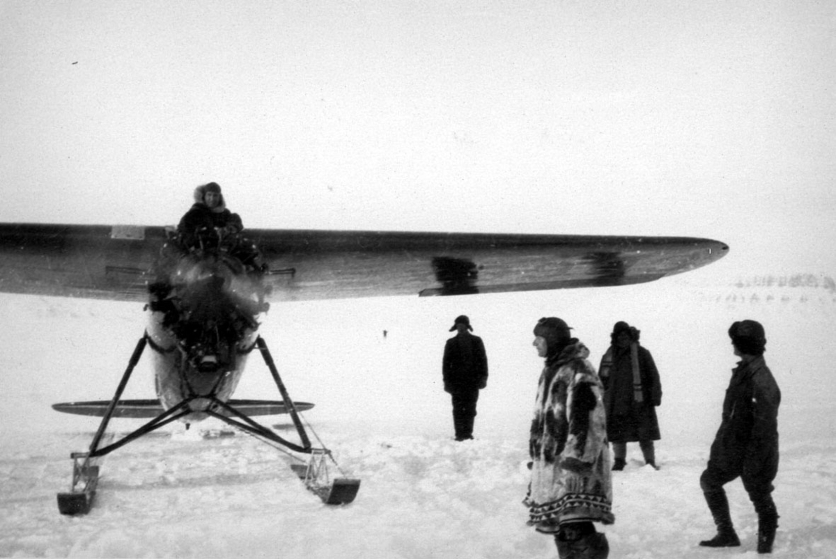 Fly, Locheed Vega, med skiunderstell. Står på bakken, motoren er gang. En person i cockpiten. 4 andre står på bakken. Snø