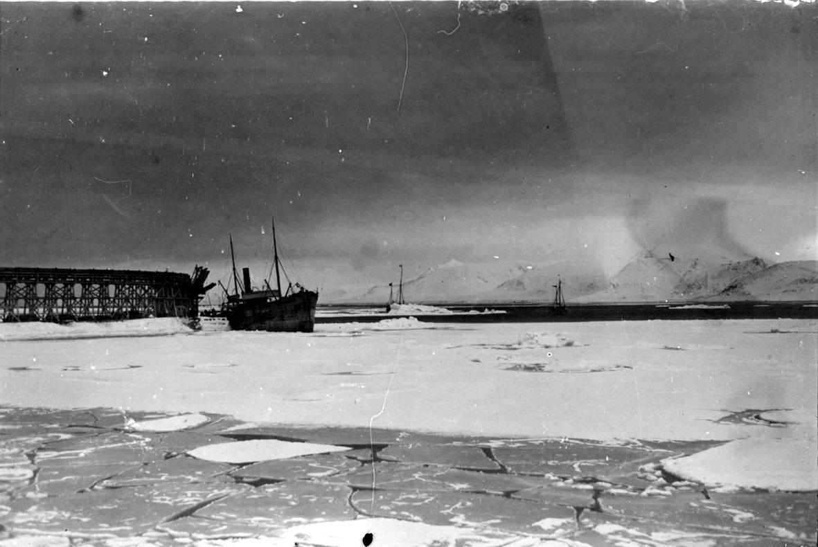 """Kaianlegg med fartøy, ant. D/S """"Alekto"""". 2 stk polarskuter, ishavsskuter bak. Is og snø."""