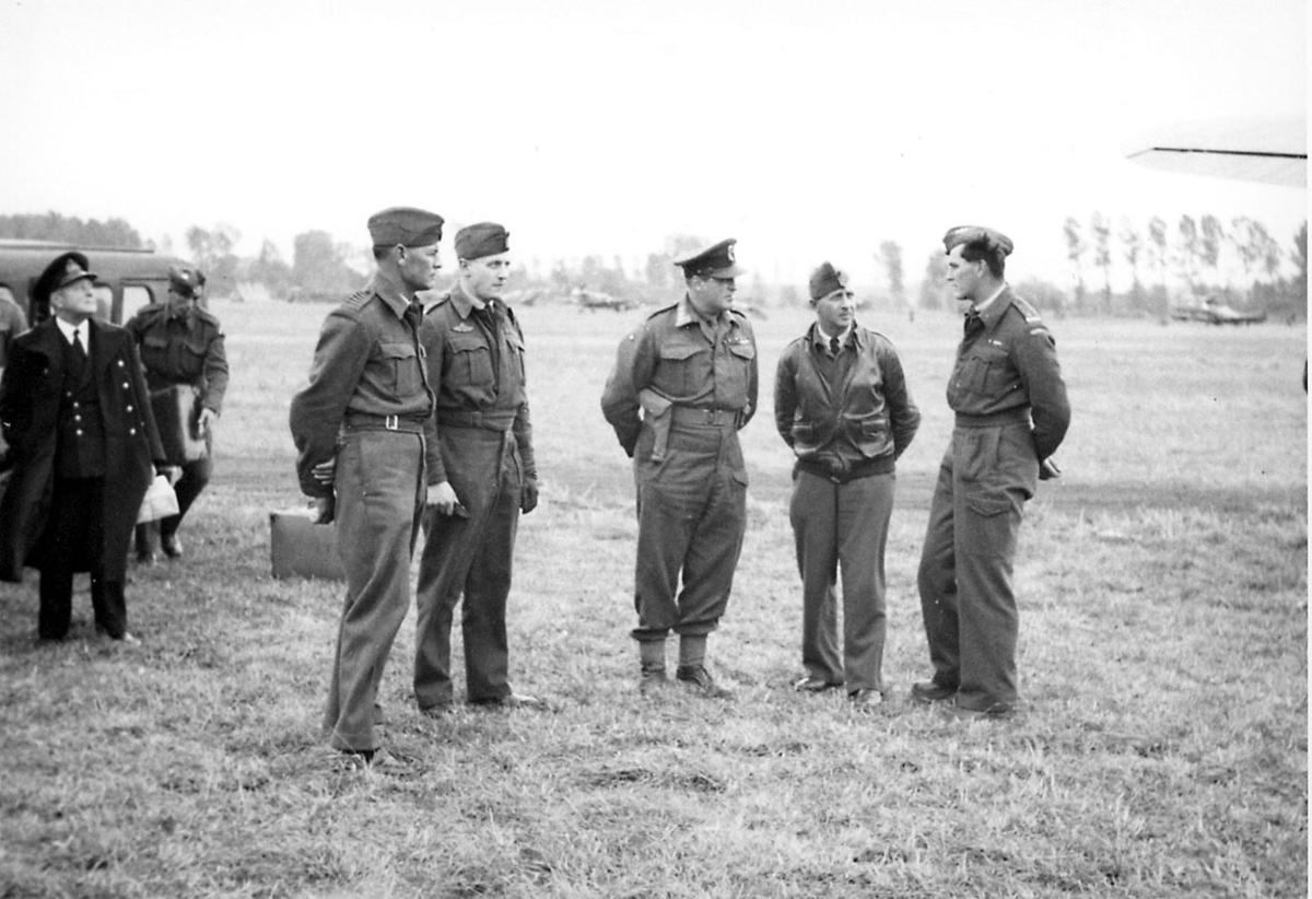 En gruppe personer, i militæruniform, tatt utendørs. Kronprins Olav i midten