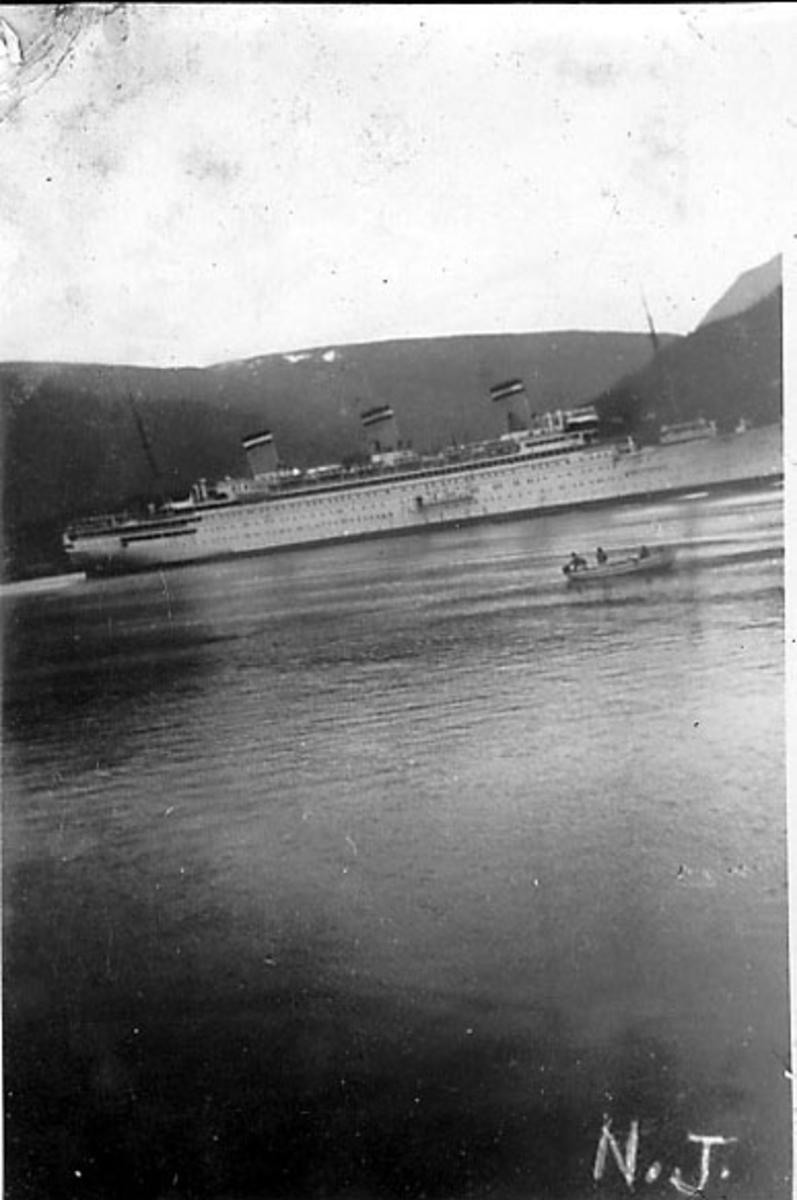 Fjord med større fartøy. Dampskip, turistbåt, sett fra siden. Foran ligger en mindre åpen båt med noen personer ombord.. Fjell i bakgrunnen. N.J. skrevet for hånd på bildet.