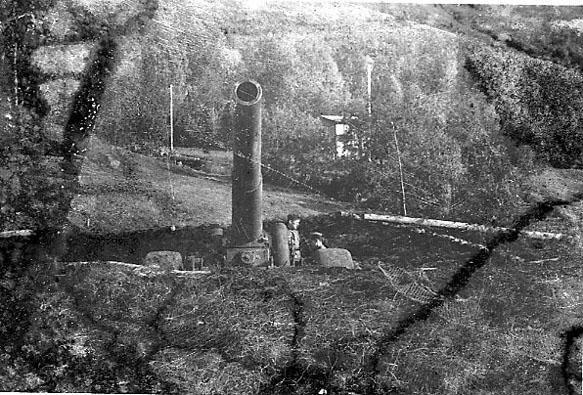 Våpen. Grop i bakken, med en større kanon montert. Løpet vender i mot. 2 personer ved kanonen, militære. Bygning mellom trærne bak.
